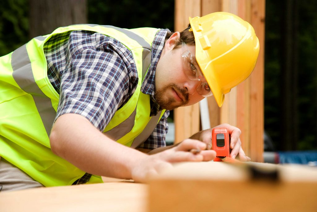 Close up of builder with tape measure